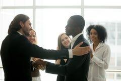 Босс компании повышая Афро-американского работника с рукопожатием Стоковая Фотография