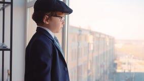 Босс мальчика ребенк в костюме с портфелем в его руке смотрит окно в его офисе Взрослая пародийность жизни, съемка крана видеоматериал