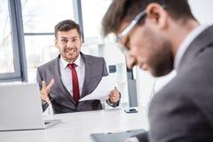 Босс смотря коллеги осадки на деловой встрече Стоковое фото RF