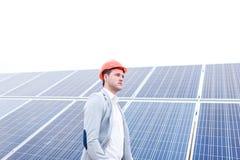 Босс стоит косым на фоне панелей солнечных батарей стоковые фотографии rf