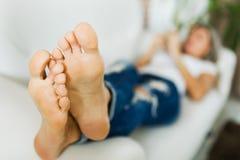 Босые ноги женщины в джинсах используя умный телефон босые ноги стоковые фотографии rf