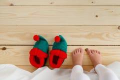 Босые ноги малого ребенк стоя на деревянном поле, просыпающся в утре, идя нести ботинки эльфа s Непознаваемый ребенок дальше Стоковое фото RF