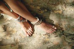 Босые ноги молодой женщины на поверхности дерева с boho вводят ювелирные изделия в моду Стоковые Фотографии RF