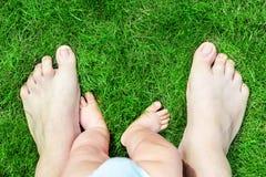 Босые ноги отца и сына на лужайке зеленой травы на парке Родитель при ребёнок делая первые шаги в жизни Исследовать ребенка стоковые изображения rf