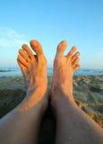 2 босые ноги человека на заходе солнца Стоковое Изображение