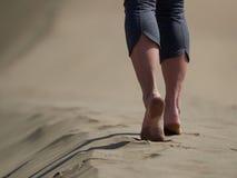 Босые ноги jogging молодой женщины/идя на пляж на восходе солнца Стоковое Изображение
