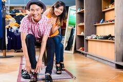 Ботинки азиатских пар покупая в магазине Стоковая Фотография