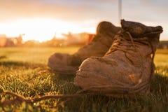 Ботинки безопасности на строительной площадке предусматриванной в грязи перед ярким заходом солнца стоковое фото