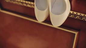 Ботинки белых женщин висят на краю деревянной кровати Славный конец-вверх r акции видеоматериалы