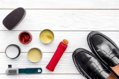 Ботинки блеска Обуйте заботу с заполированностью, щетками, воском, губкой Белое деревянное spacee взгляд сверху предпосылки для т стоковые фотографии rf