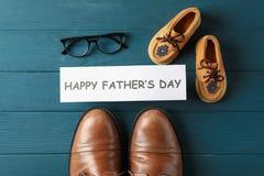 Ботинки Брауна кожаные, ботинки детей, день отцов надписи счастливый, и стекла на деревянной предпосылке стоковые изображения