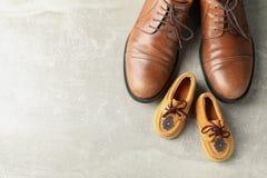 Ботинки Брауна кожаные и ботинки детей на серой предпосылке, космосе для текста стоковая фотография rf