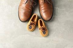Ботинки Брауна кожаные и ботинки детей на серой предпосылке, космосе для текста стоковое изображение rf