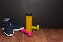 Ботинки, гантели и бутылка фитнеса сока на деревянном поле Стоковые Фотографии RF