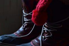 Ботинки зимы и красная крышка Стоковые Изображения