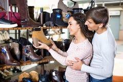Ботинки зимы молодых пар покупая в обувном магазине Стоковые Изображения
