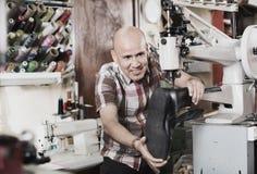 Ботинки зрелого рабочего класса шить кожаные на токарном станке стежком Стоковая Фотография