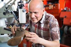 Ботинки зрелого рабочего класса шить кожаные на токарном станке стежком Стоковая Фотография RF