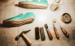 Ботинки и аппаратуры на таблице на мастерской обуви Стоковое фото RF