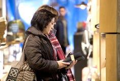 Ботинки и цены покупателя наблюдая Стоковые Изображения
