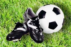 Ботинки и шарик футбола на предпосылке зеленой травы Стоковое Изображение