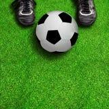 Ботинки и шарик футбола на поле с космосом экземпляра Стоковое Фото