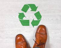 Ботинки классических людей с рециркулируя символом на поле Стоковое Фото