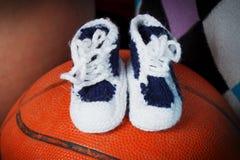 Ботинки младенца на шарике корзины стоковое фото rf