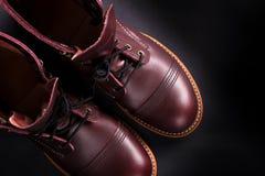 Ботинки модных людей кожаные коричневые на черной предпосылке Ботинки людей высокие Взгляд сверху скопируйте космос Стоковое Фото