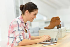 Ботинки молодой женщины покупая на интернете Стоковая Фотография