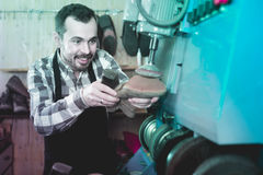 Ботинки мужского работника фиксируя неудачные в мастерской ремонта ботинка Стоковая Фотография RF