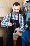 Ботинки мужского работника фиксируя неудачные в мастерской ремонта ботинка Стоковая Фотография