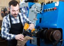 Ботинки мужского работника фиксируя неудачные в мастерской ремонта ботинка Стоковое Фото