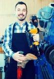 Ботинки мужского работника фиксируя неудачные в мастерской ремонта ботинка Стоковое фото RF