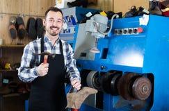Ботинки мужского работника фиксируя неудачные в мастерской ремонта ботинка Стоковое Изображение RF