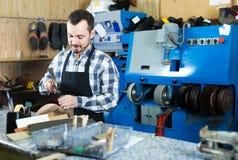 Ботинки мужского работника фиксируя неудачные в мастерской ремонта ботинка Стоковые Фото