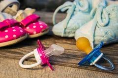 Ботинки младенца и pacifiers украшают дырочками и синь на старой деревянной предпосылке Стоковые Фото