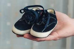 Ботинки младенца на родительской руке Стоковое фото RF