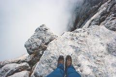 Ботинки ног путешественника на скале скалистой горы Стоковая Фотография