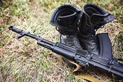 Ботинки лодыжки солдата и конец-вверх штурмовой винтовки автомата Калашниковаа Стоковые Фотографии RF