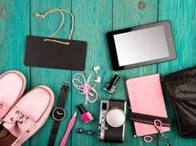 ботинки, ПК таблетки, камера, сумка, блокнот, вахта, наушники и предметы первой необходимости на голубом деревянном столе Стоковые Изображения