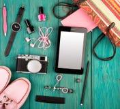 ботинки, ПК таблетки, камера, сумка, блокнот, вахта, наушники и предметы первой необходимости на голубом деревянном столе Стоковое Изображение
