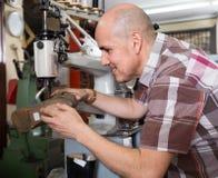 Ботинки пожилого рабочего класса шить кожаные на токарном станке стежком в мастерской Стоковые Фотографии RF