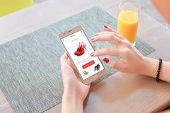 Ботинки покупки женщины красные онлайн Передвижные app или вебсайт на экране стоковое фото rf