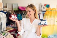 Ботинки покупок беременной женщины для ее младенца Стоковое фото RF