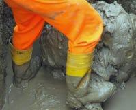 Ботинки работника в коричневой грязи во время потока 5 Стоковые Изображения