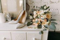 Ботинки свадьбы и личное имущество свадьбы, кольца золота свадьбы, букет свадьбы на дрессере Стоковое Фото