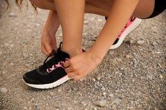 Ботинки связи бегуна женщины на дороге горы Стоковое фото RF