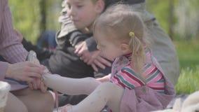 Ботинки связи матери небольшой прелестной белокурой дочери в парке и другой матери huging ее молодой сын пока сидящ в видеоматериал