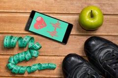 Ботинки спорт, Яблоко, измеряя лента и телефон с карточкой здоровья на деревянной предпосылке Передвижной датчик здоровья app для Стоковая Фотография RF